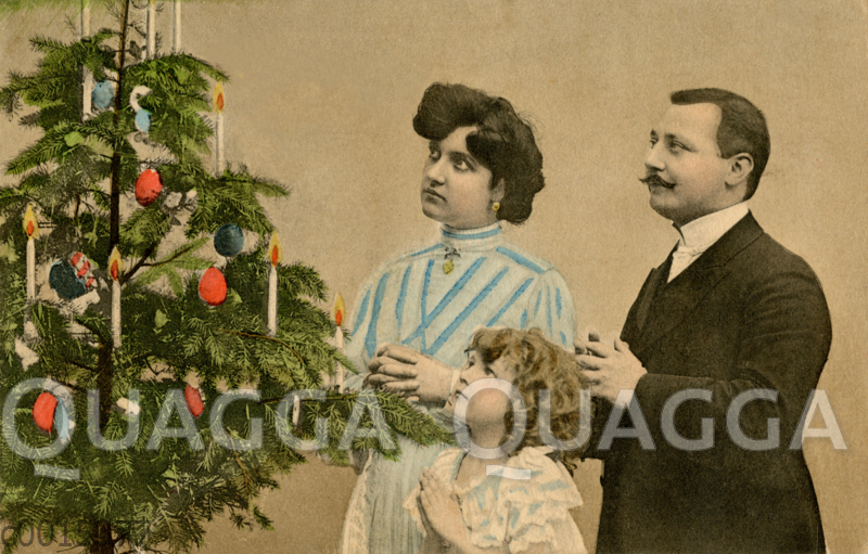 Familie betend am Weihnachtsbaum