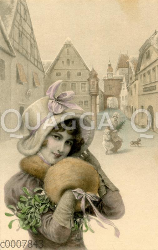 Junge Frau mit Muff und MIstelstrauß vor Weihnachten