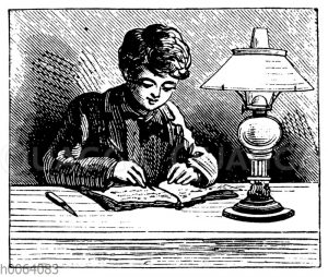 Junge schreibt beim Licht einer Lampe